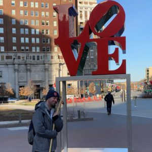 a man posing with his wooden lacrosse stick at the Love Sculpture in Philadelpha